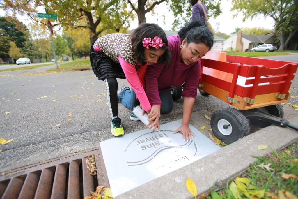 Young and older neighbors work together to stencil a storm drain that will help keep leaves from getting in, thus help improve the water quality of the nearby lake.