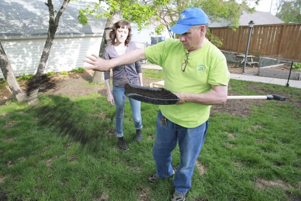 Dahm distributes organic compost over Berg's yard.